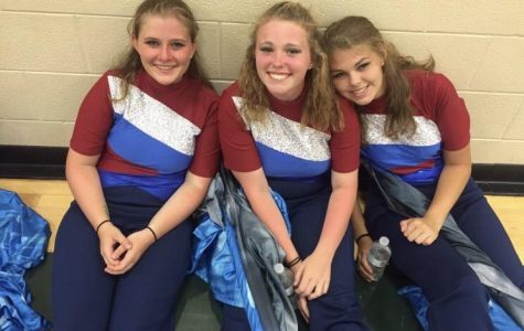 Nadzam, Brenna Ryan and Amanda Jarrell pose in their flag line uniforms.