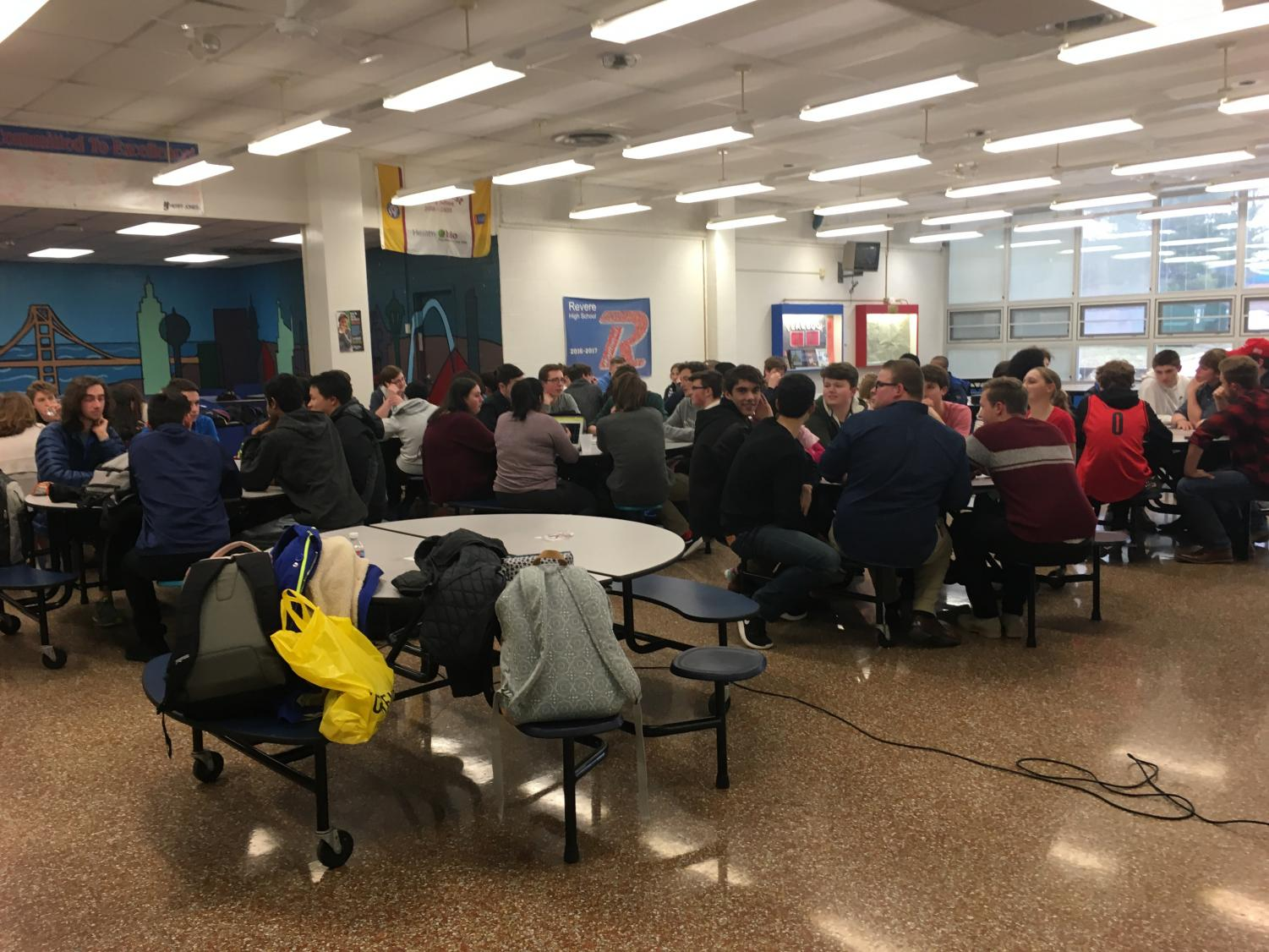 Students converse at different tables in the middle ground event, which was held in the cafeteria on February 14.