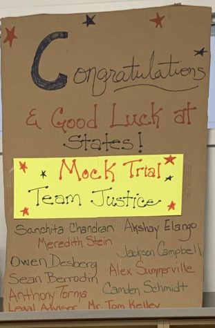 A sign hangs congratulating Team Justice on their qualification.