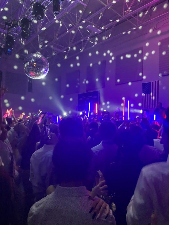 Students in the gym enjoy the disco ball and party.