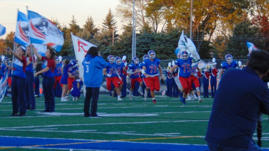 The football players, led by senior Colton Carmichael, charge through the banner.
