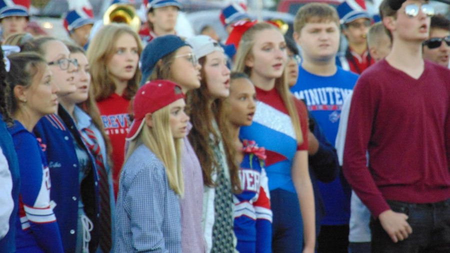 Choir and band students stand together, singing the National Anthem at the beginning of the football game.